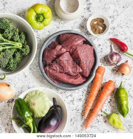 Raw ingredients for cooking lunch - beef meat and vegetables on a light background top view