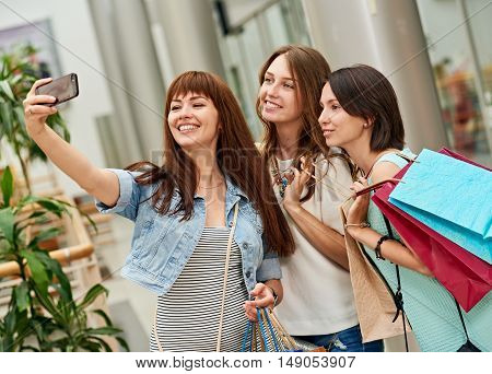 Beautiful girls with shopping bags taking a selfie their cell phone