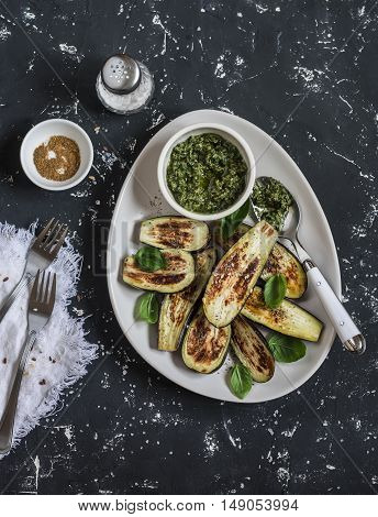 Baked eggplant and pesto sauce. On a dark background top view
