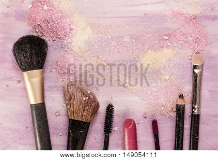 Makeup brushes, lipctick and pencil on a light purple background, with traces of powder and blush on it. A horizontal template for a makeup artist's business card or flyer design, with copyspace