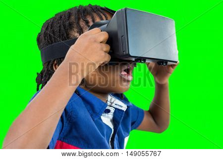 Profile view of little boy holding virtual glasses against green vignette
