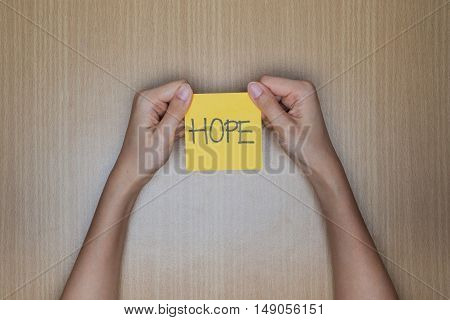 Hope word in hand word on piece tear paper