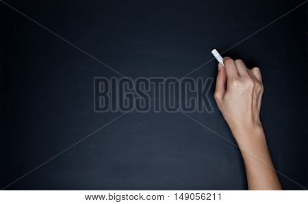 The human hand starts writing with chalk on a clean blackboard