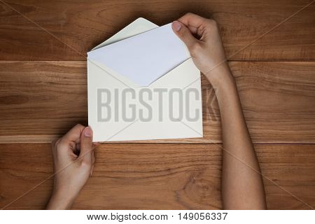A female(woman) hand hold(open) a envelope and post card on the wood desk top view at the studio.
