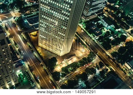 Tokyo - Aerial night view with office building and glowing light trails from traffic. Shinjuku. May 2016