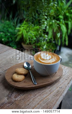 cup of coffee and cookie in coffee shop vintage color