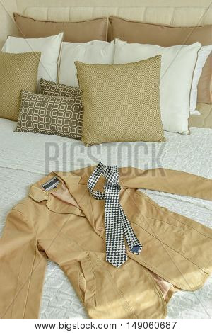 Suit And Necktie On Bed With Brown And Biege Pillows