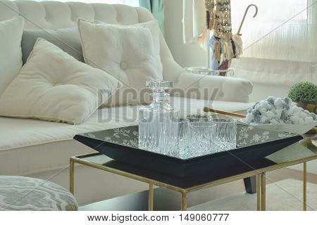 Crystal Bottle And Glasses On Table With Beige Sofa In Living Room