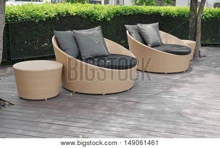 Outdoor artificial rattan with pillow on wooden floor