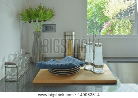 Dishes and glass bottles setting on black counter top in the kitchen