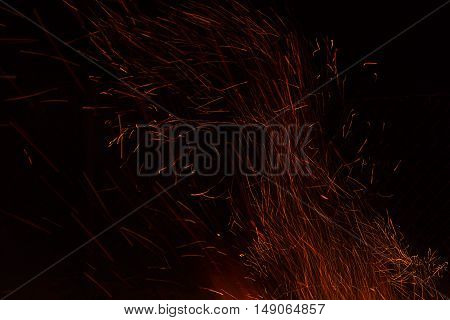 Red and orange fire background of flame and sparks from the bonfire in the form of tracks on a black background