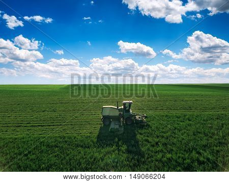 Tractor mowing green field and bkue sky with clouds