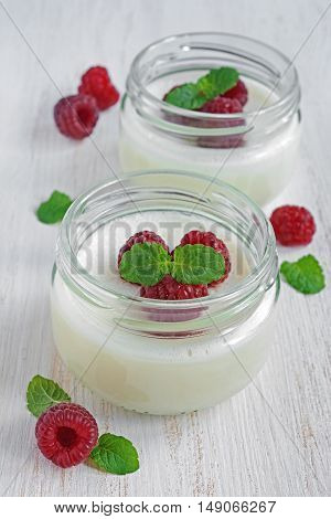 Delicious creamy mousse with fresh raspberries in glass jars
