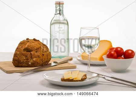 Healthy summer lunch spread out on a tale with a crusty loaf of bread sandwich cheese and bowl of ripe red tomatoes accompanied by fresh water to drink
