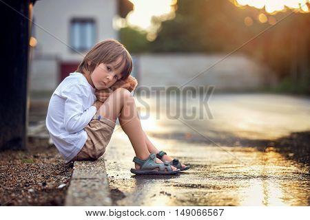 Sad Little Boy, Sitting On The Street In The Rain, Hugging His Teddy Bear