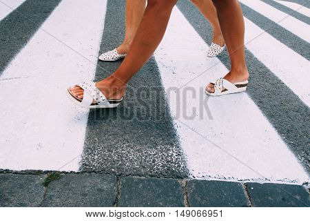 Female legs in white shoes going on pedestrian zebra. Women crossing road on crosswalk. City life, traffik, walking concept