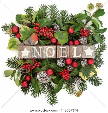 Christmas decoration with noel sign in old wooden blocks, robin and red bauble decorations, holly, ivy , snow covered pine cones and fir leaf sprigs over white background.
