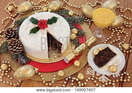Traditional christmas cake and slice with holly, snow covered winter greenery, eggnog, gold bauble decorations and foil wrapped chocolate balls over oak background.