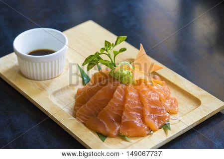 Salmon raw sashimi slice on wooden plate