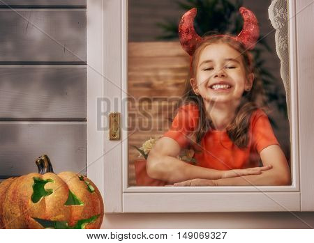 Happy Halloween! Cute cheerful kid looking on the window. Beautiful child girl in devil costume in the house decorated to Halloween.
