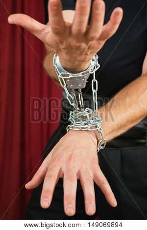 Hands in chains low key, vertical image, color image