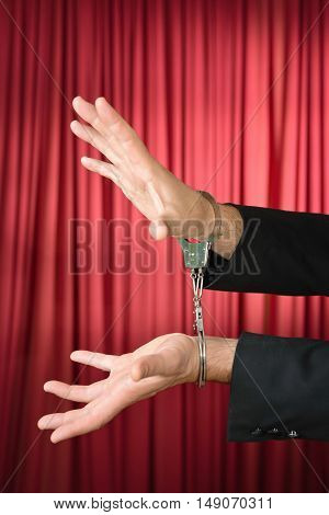 Cuffed hands of an escape artist, vertical image, color image