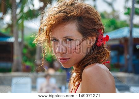 Sexy woman with red flower in her head on the beach