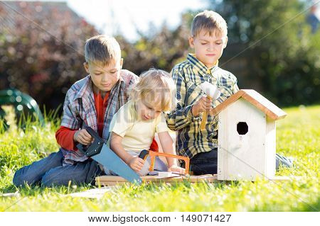 Three boys - two teenagers and one preschooler making together nesting box sitting on lawn in summerday