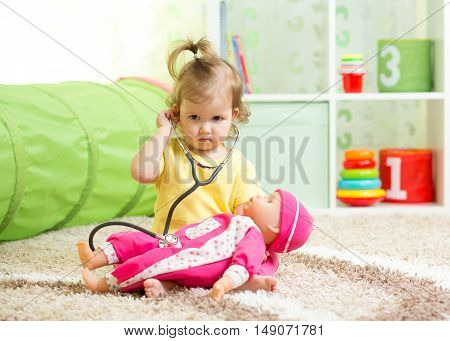 Kid Girl Playing Doctor With A Doll In Playroom
