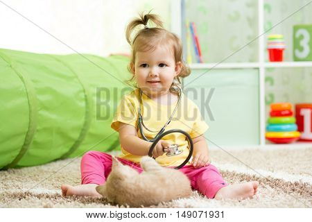 Child Girl Playing Doctor With A Cat In Nursery