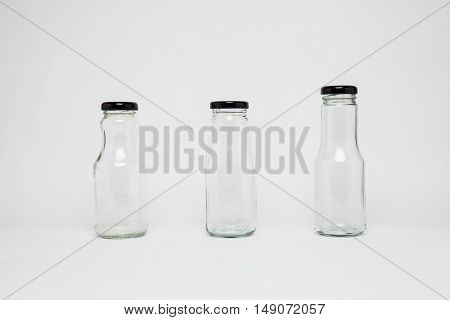 isolated three milk bottle, in a studio