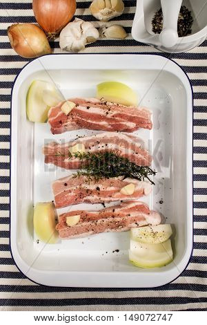 fat raw pork belly with onion garlic crushed black peppercorn and thyme in an enamel roasting tin