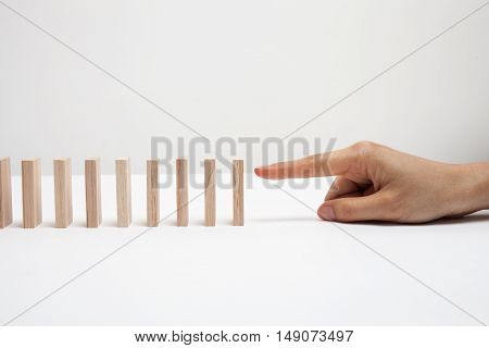 hand with white wooden toy on a white background