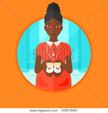 An african-american young pregnant woman holding baby booties in hands. Smiling pregnant woman holding baby booties on the belly. Vector flat design illustration in the circle isolated on background.