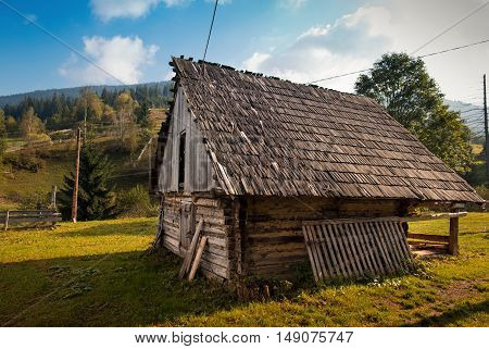 Old abandoned wooden house on green grass in the highlands