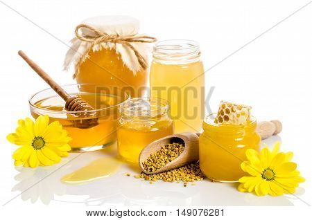 The bank of honey with honeycombs glass bowl with honey and wooden scoop with pollen