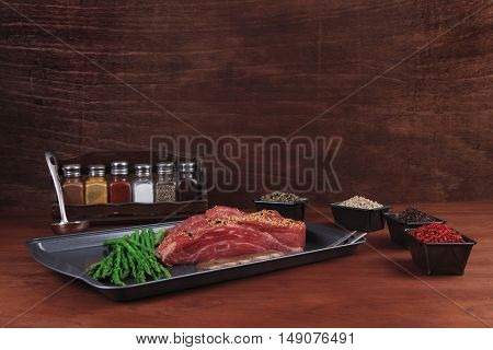 meat raw beef fillet chunk on black tray asparagus on wooden table allspice pink white black green peppercorn empty space for text