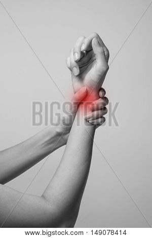 Wrist injury woman holds a hand on her pain wrist.