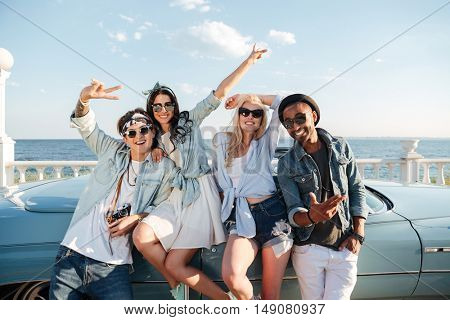 Group of cheerful young friends standing outdoors and showing peace sign