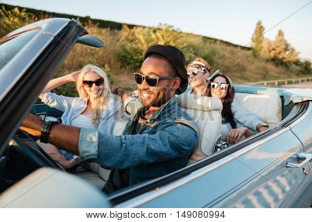 Group of cheerful young friends driving car and smiling in summer