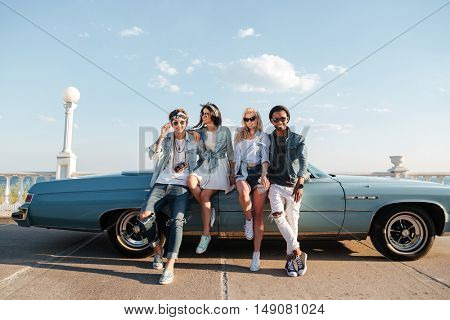 Happy young friends standing together near vintage car