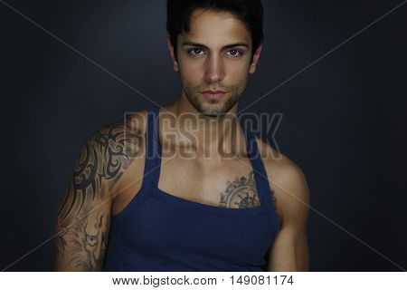 Handsome male wearing a top tank over a gray background