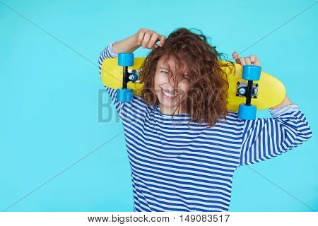 Woman skater. Curly girl holding a yellow skateboard