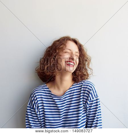 Square portrait of hipster woman laughing with eyes closed on white background. Curly cute girl smiling