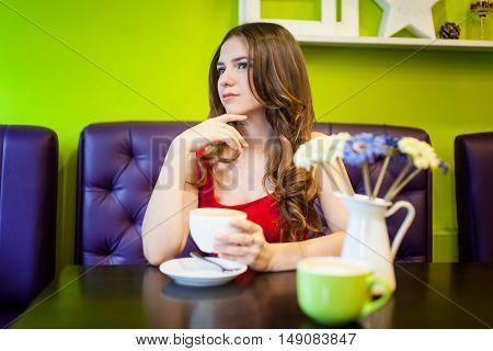 Young teenager girl is drinking coffee in a cafe