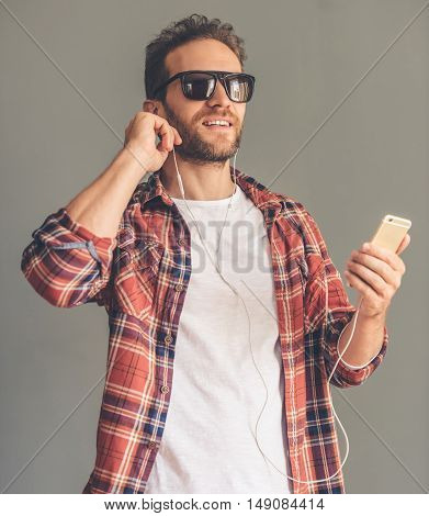 Handsome stylish young man in casual clothes sun glasses and earphones is listening to music using a smart phone and smiling on gray background