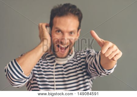 Handsome stylish young man in sailor's striped vest is listening to music using headphones looking at camera screaming and showing Ok sign on gray background