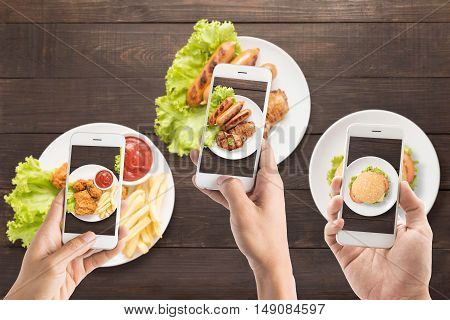 Friends Using Smartphones To Take Photos Of Sausage, Pork Chop, Fries Chicken And Burger