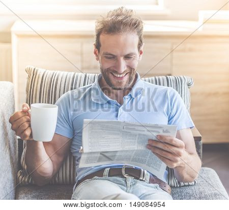 Handsome young businessman in casual clothes is reading newspaper holding a cup of coffee and smiling while resting on couch at home