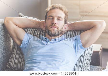 Handsome young businessman in casual clothes is holding hands behind head while napping on couch at home